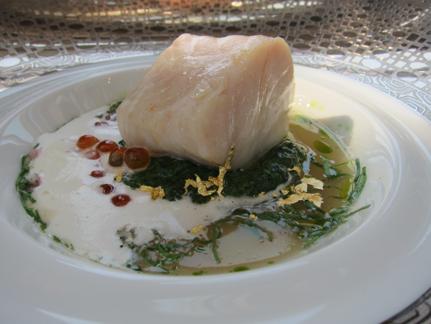 Slow cooked Black Cod in virgin oil topped with salmon roes served in a watercress broth and shiso flower