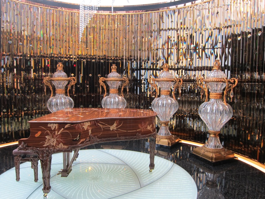 The lift opens up to an opulent mirrored foyer, with a pianist playing on a beautifully hand-carved and inlaid piano...